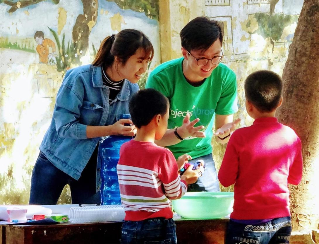 Two Projects Abroad volunteers in Vietnam help teach kids proper hand washing techniques